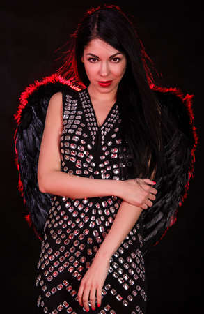 Beautiful young woman with black angel wings over dark red background