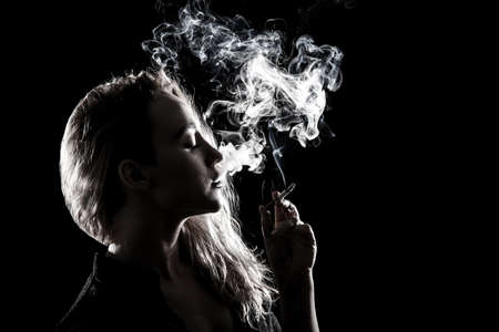 dark girl: Beautiful young woman smoking a cigarette over black background