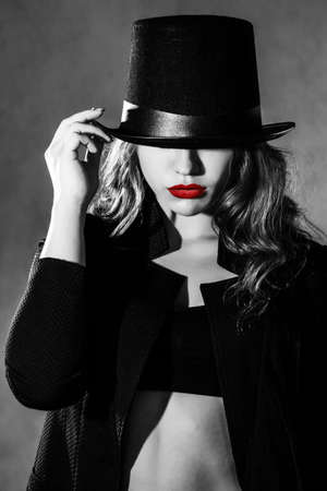 uncombed: Beautiful young woman in a black hat and a black jacket Stock Photo