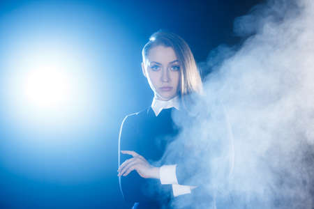 reproach: Beautiful young woman behind the cloud of blue smoke