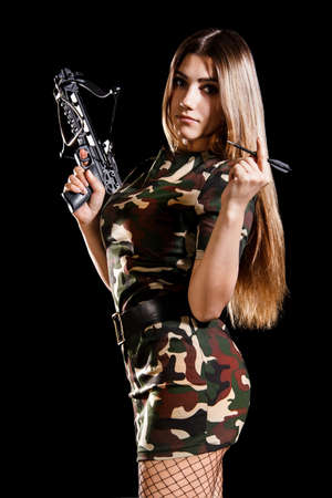 arbalest: Military woman loading the arbalest over black background