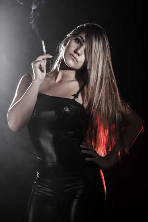 pernicious habit: Beautiful young woman in a leather clothes smoking a cigarette over black background
