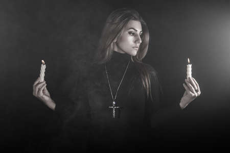 turbid: Lonely young woman holding two candles in a smoke