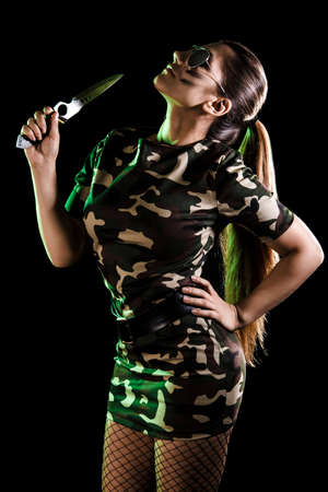 cuchillo: Mujer militar con un cuchillo sobre fondo negro