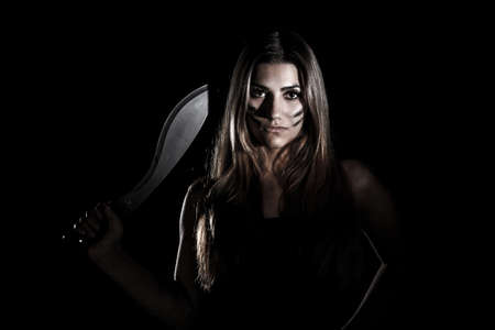 Woman with a huge knife in the darkness Stock Photo