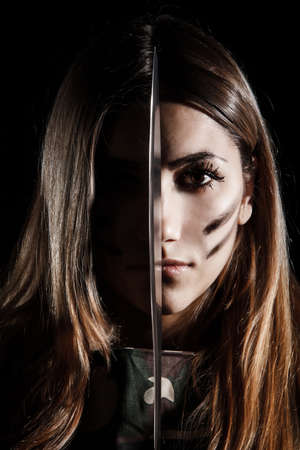 Military woman holding a knife at the middle of her face