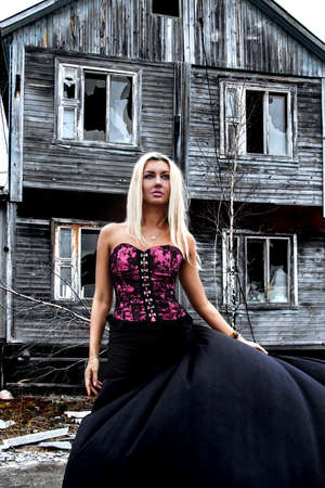 winy: Gorgeous woman at the background of the abandoned wooden house