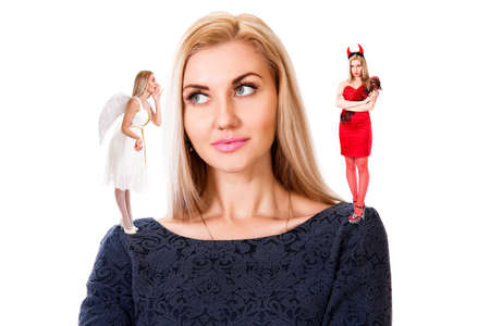 Beautiful young woman with small angel and demon on her shoulders isolated over white background Stock Photo