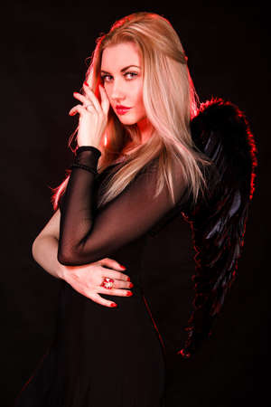 succubus: Beautiful young woman with black wings over black background Stock Photo