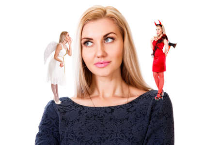 Beautiful young woman with small angel and demon on her shoulders isolated over white background Фото со стока