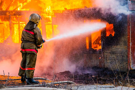 fireman: Fireman extinguishes a fire in an old wooden house Stock Photo