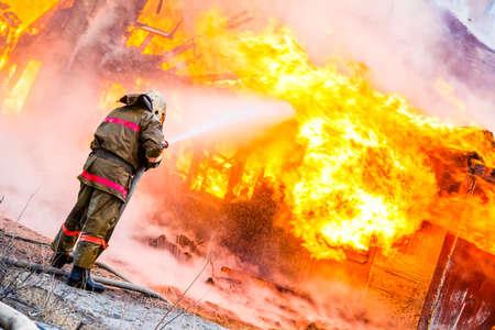 incendio casa: Bombero extingue un incendio en una vieja casa de madera Foto de archivo