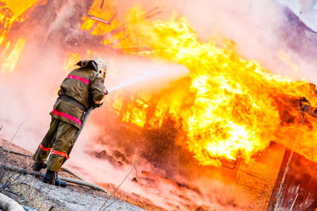 fire rescue: Fireman extinguishes a fire in an old wooden house Stock Photo