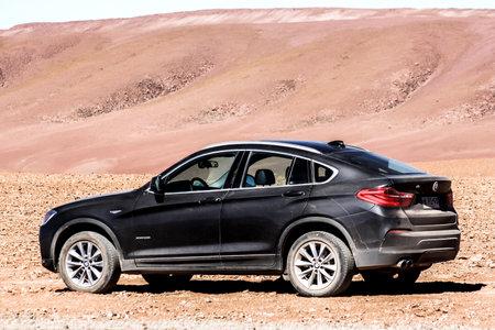 ANTOFAGASTA, CHILE - NOVEMBER 16, 2015: Dirty black crossover BMW F26 X4 in the desert.