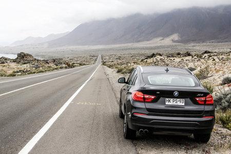 crossover: ATACAMA, CHILE - NOVEMBER 14, 2015: New black crossover BMW F26 X4 at the roadside.