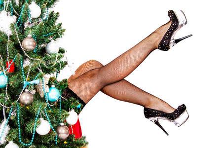 pies sexis: Piernas atractivas de la mujer detrás del árbol de navidad aislado más de fondo blanco Foto de archivo