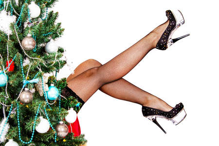 stocking feet: Sexy woman legs behind the Christmas tree isolated over white background