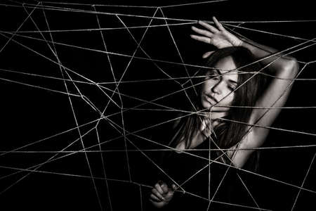 entangled: Young woman entangled the net of ropes over black background