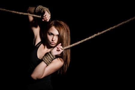 Schöne junge Frau mit gebundenen Armen auf schwarzem Hintergrund