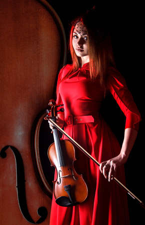 violinist: Beautiful young violinist in a red dress over black background Foto de archivo