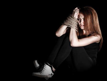 Schöne junge Frau mit gebundenen Armen auf dem Boden auf schwarzem Hintergrund sitzt