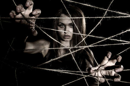 emaciated: Pale woman snatching the ropes over black background Stock Photo