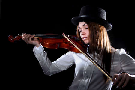 instruments: Pretty young woman playing a violin over black background