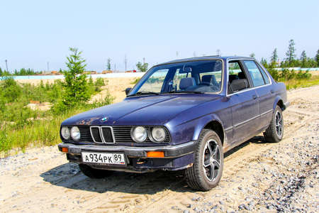 contorted: NOVYY URENGOY, RUSSIA - JULY 17, 2013: Motor car BMW E30 324d at the countryside.