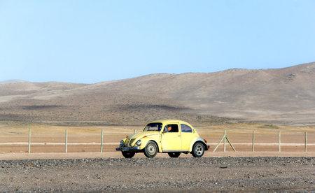 escarabajo: ATACAMA, CHILE - 18 de noviembre, 2015: coche de motor retro del escarabajo de Volkswagen se mueve en la carretera Panamericana a través del desierto de Atacama.