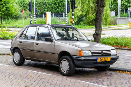 outside machines: AMSTERDAM, NETHERLANDS - AUGUST 10, 2014: Motor car Peugeot 205 in the city street.