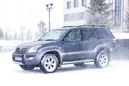 4wd: NOVYY URENGOY, RUSSIA - MARCH 20, 2016: Motor car Toyota Land Cruiser Prado at the city street during a heavy northern blizzard.