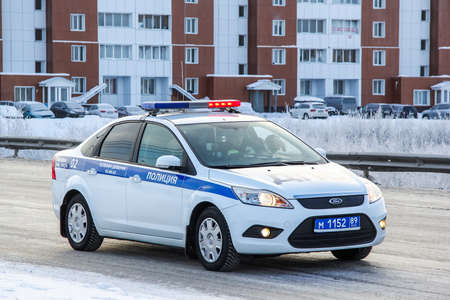 escorting: NOVYY URENGOY, RUSSIA - NOVEMBER 4, 2013: Police motor car Ford Focus in the city street escorting the Sochi 2014 Olympic Fire relay race. Editorial
