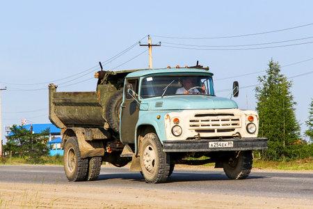 contorted: NOVYY URENGOY, RUSSIA - JULY 18, 2013: Dump truck ZIL-MMZ-4505 in the city street.