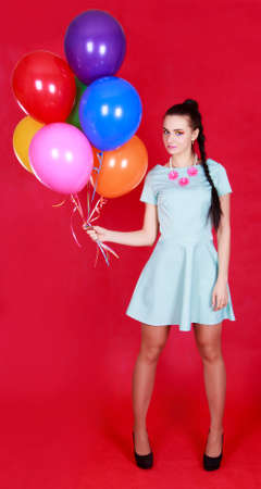 Portrait of a young attractive woman holding bunch of many bright balloons over red background