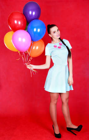 Portrait of a young attractive woman with many bright balloons over red background