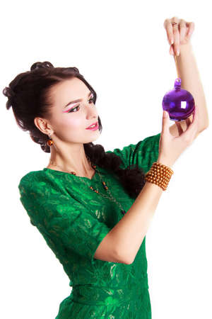 lock of hair: Portrait of a beautiful young woman in a green evening dress with a purple Christmas bauble isolated over white background
