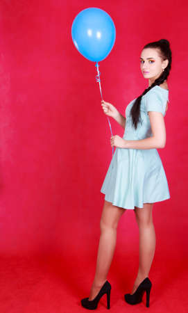 Portrait of a young attractive woman holding blue balloon over red background Stock Photo