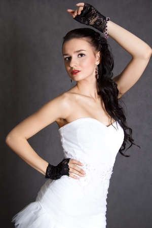 fiancee: Portrait of a young beautiful fiancee in a wedding dress and black gloves over grey background