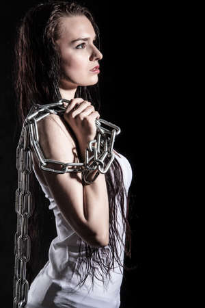 Portrait of a beautiful young woman with a steel chain over black background