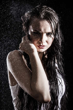 Wet sexy woman covered with water drops over black background