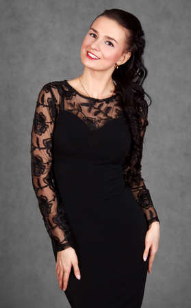 Portrait of a young attractive woman in a black evening dress over grey background