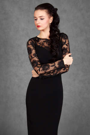 svelte: Portrait of a young attractive woman in a black evening dress over grey background