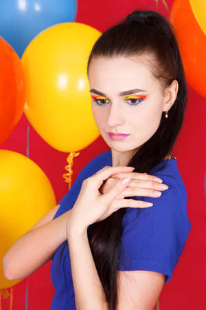 Portrait of a young attractive woman among bright balloons Stock Photo