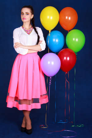Portrait of a young attractive woman near many bright balloons over blue background