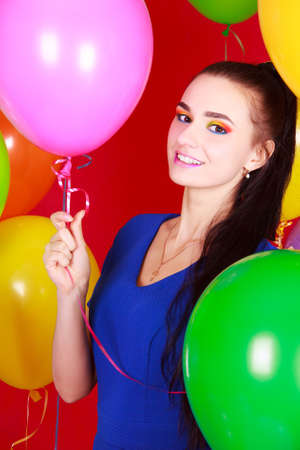 Nice young woman among many bright balloons over red background