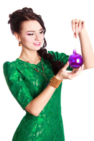 Portrait of a beautiful young woman in a green evening dress with a purple Christmas bauble isolated over white background