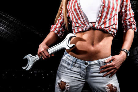 Torso of a sexy woman with a big wrench at the background of tires