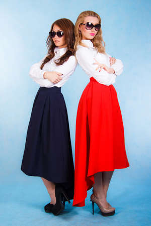 Beautiful young women in a long skirts over cyan background