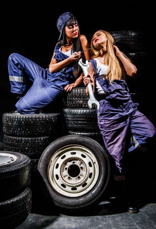 Sexy young women sitting on a tires over black background