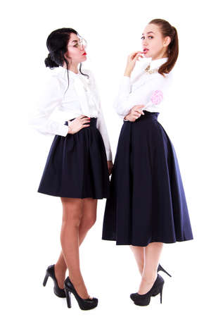 Two young women playing the teacher and the pupil isolated over white background